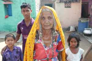 A gypsy woman outside her home wit hfamily